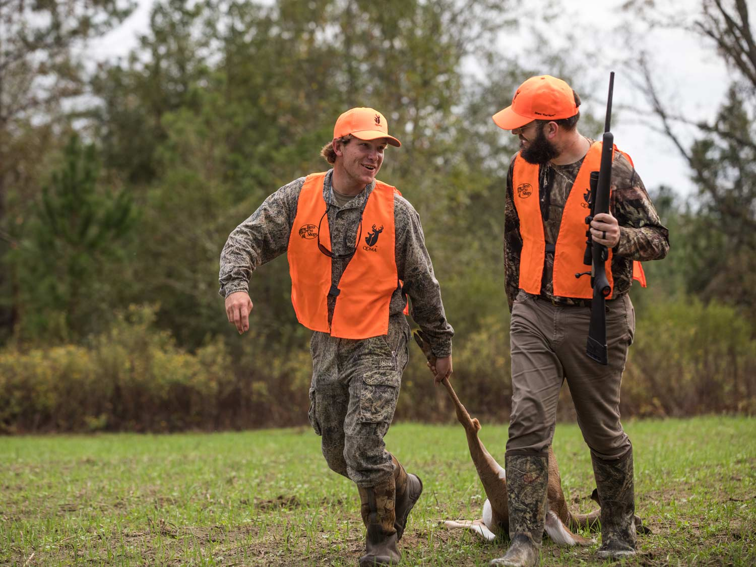 Two hunters in camo and orange vests drag a deer.