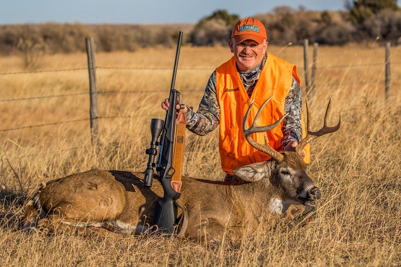 hunter with dead deer and rifle.