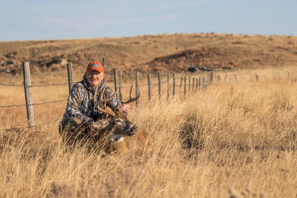 hunter with deer in field
