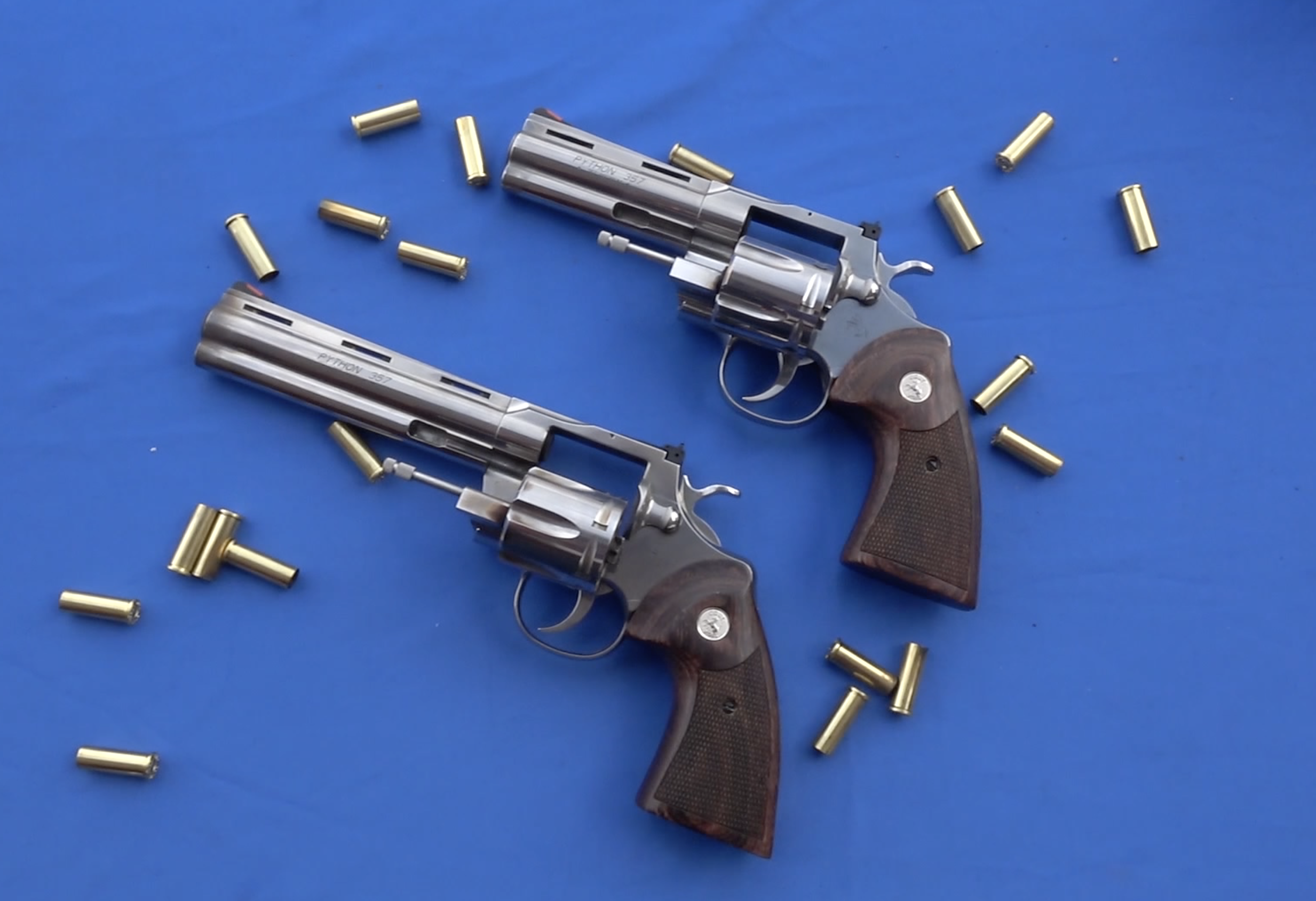 two Colt Python revolvers, one 6-inch barrel and one 4.25-inch barrel, with the wheels open on a blue background with empty cartridge cases