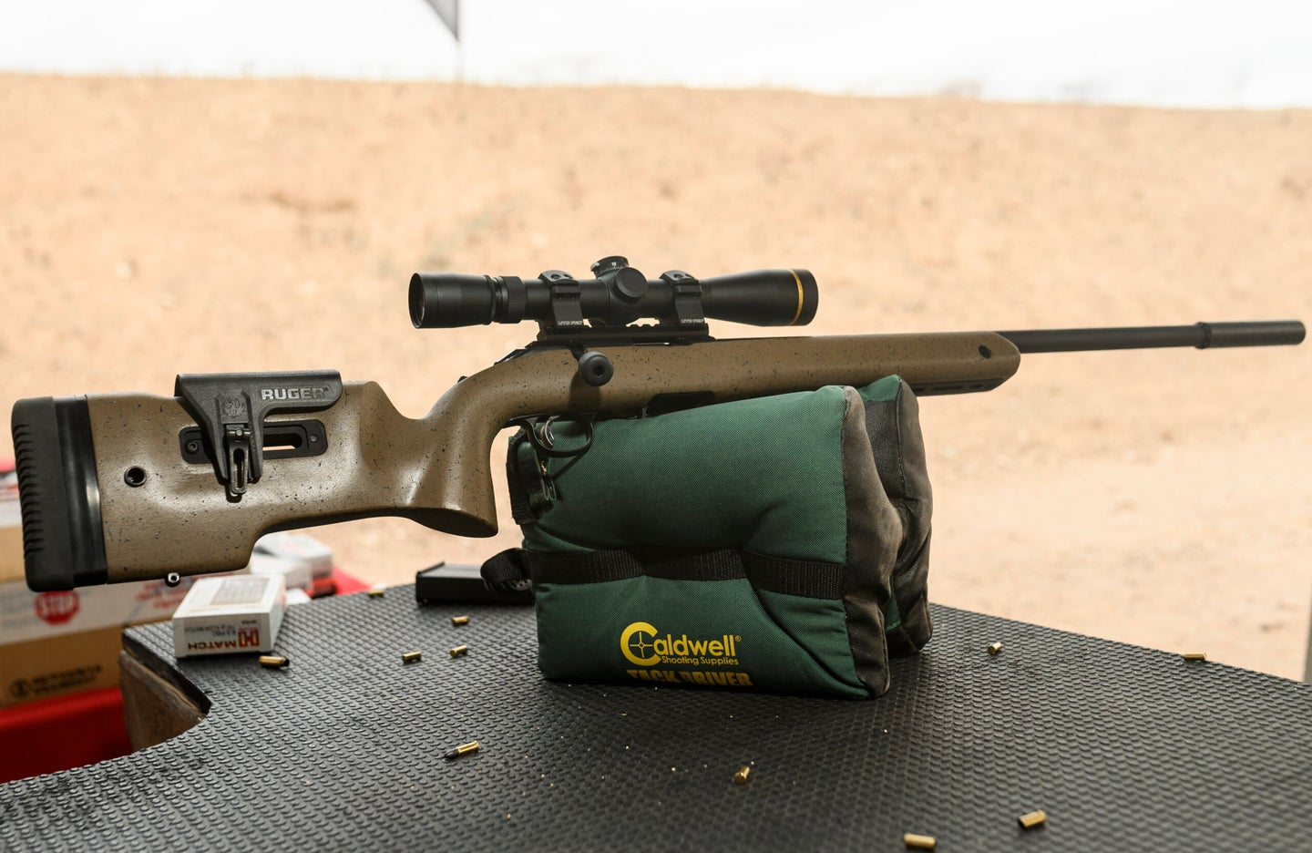a rimfire rifle resting on a shooting bag at the range with empty 22 shells on the table