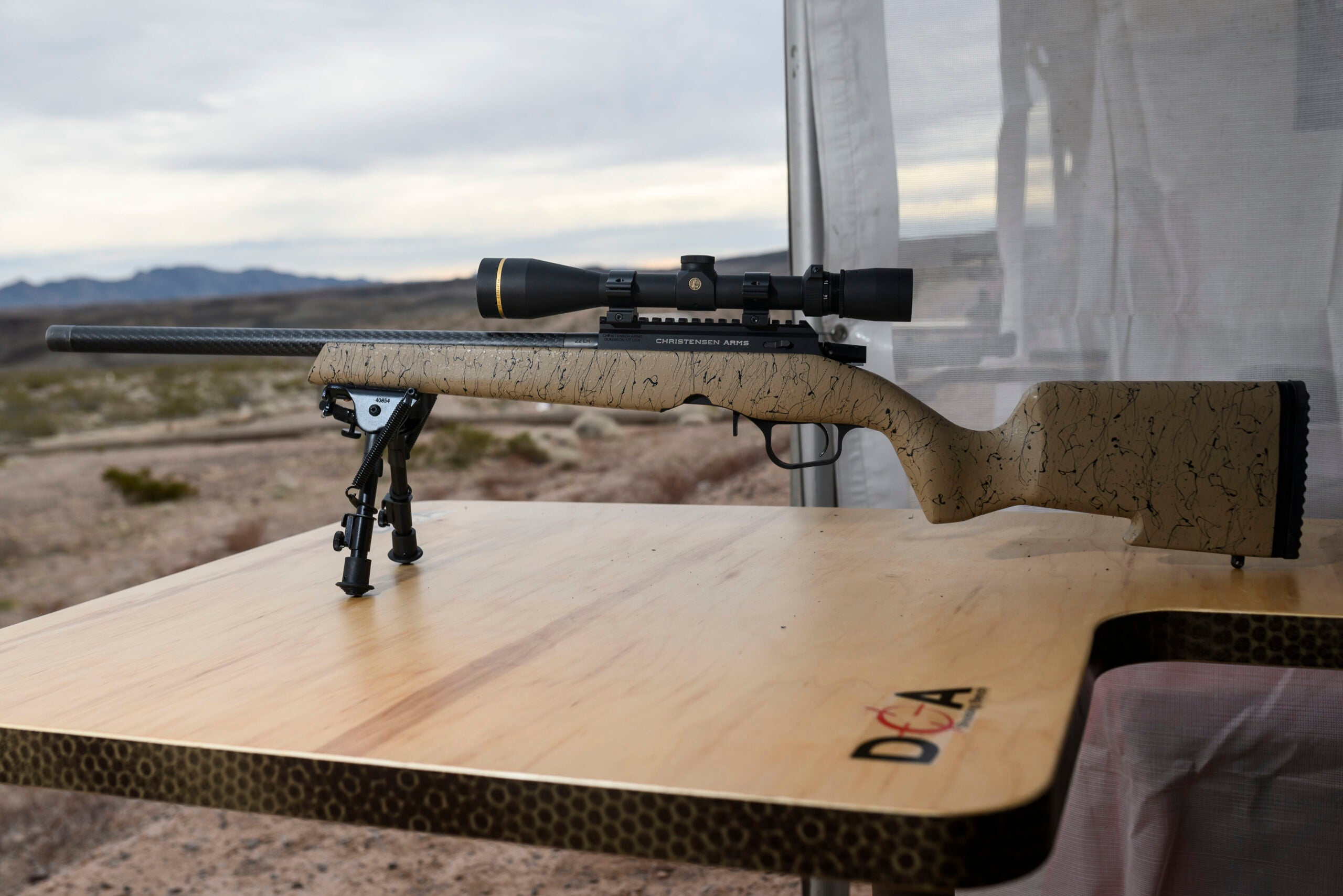 A tan Christensen Arms rimfire rifle with a scope sitting on a DOA shooting bench