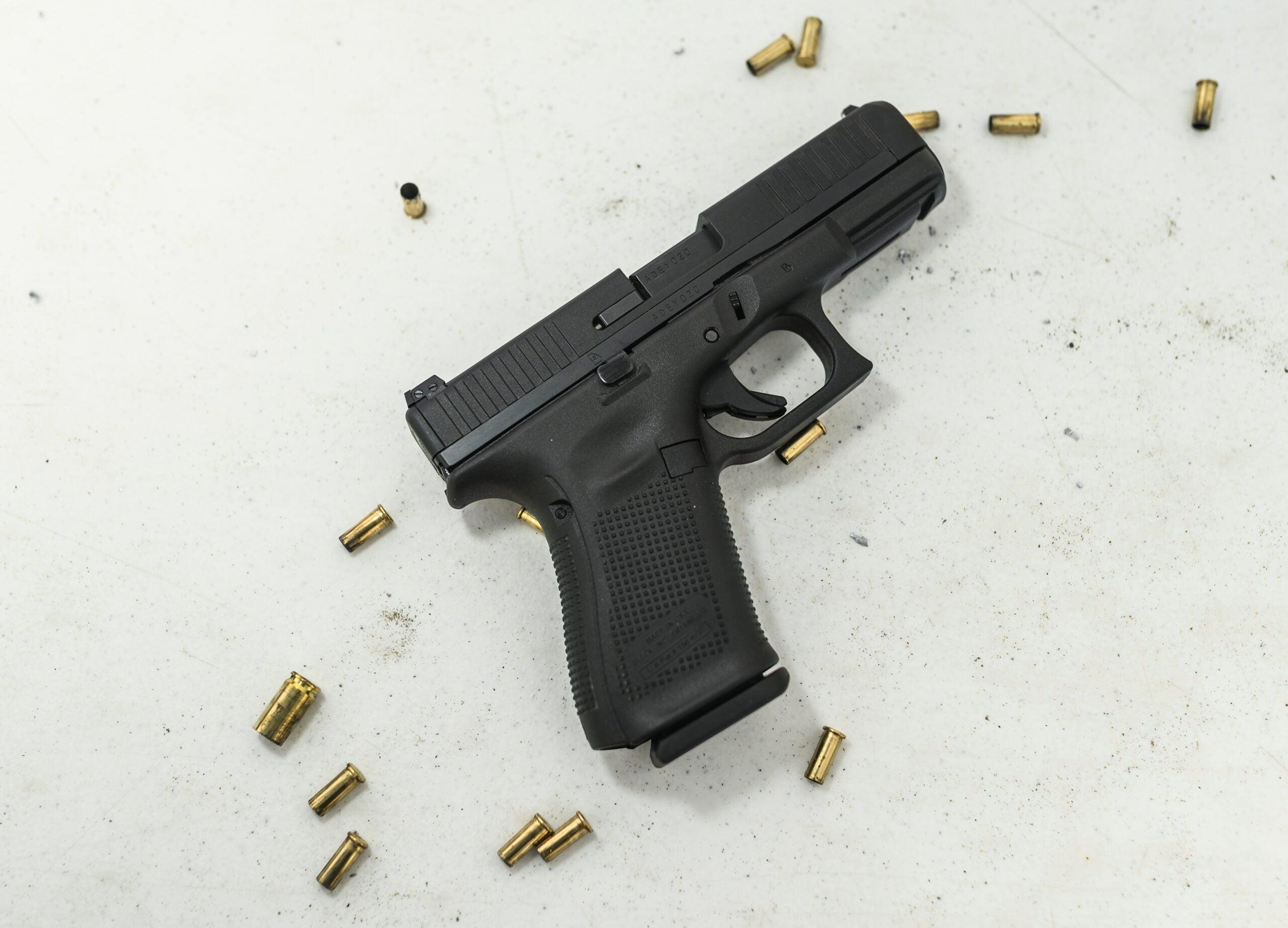 Glock G44 handgun on a white background with empty rimfire cartridge cases scattered around it