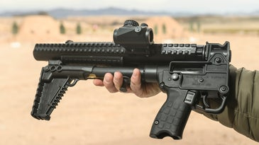 a 9mm pistol-caliber carbine, folded in half, in hand at the range