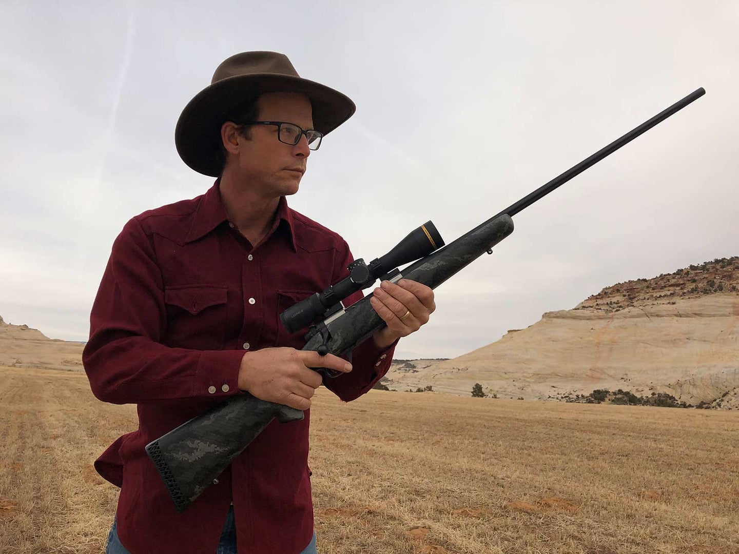 Man in cowboy hat holding a Weatherby Backcountry rifle.