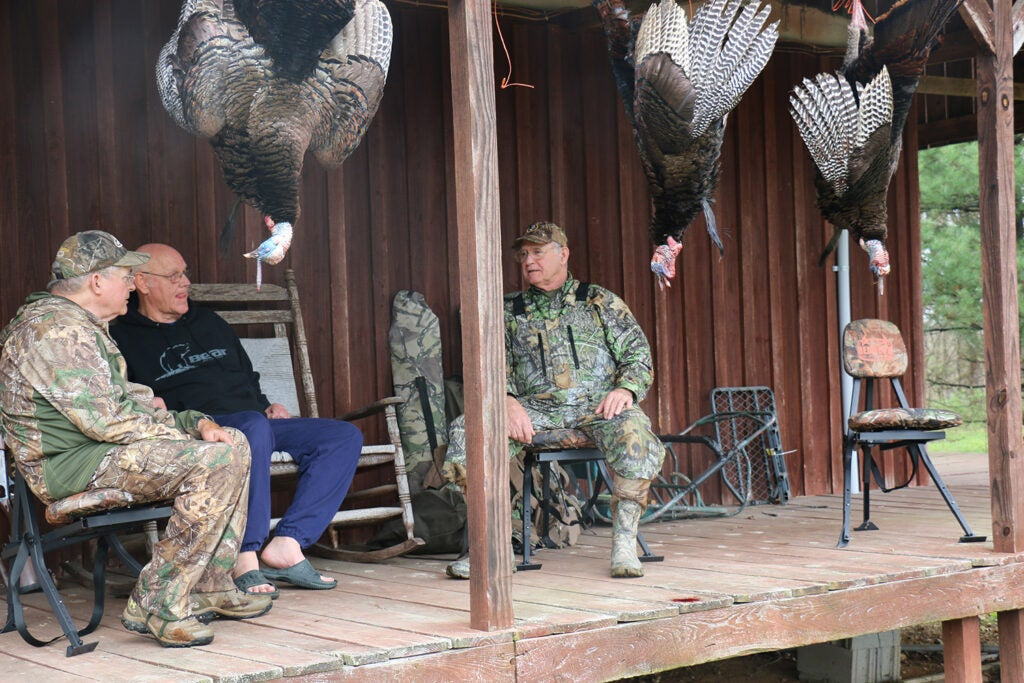 Turkey hunters sitting on a porch while turkeys hang from the porch.