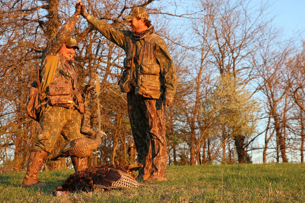 Two turkey hunters standing over a turkey.