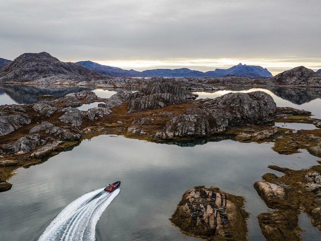 A lone boat in a sound of Greenland.