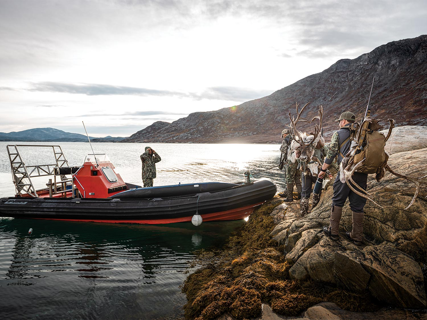 Caribou hunters next to a hunting guide boat.
