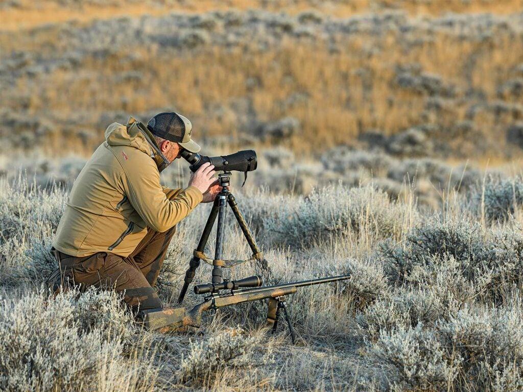 Hunter using a spotting scope in an open field.