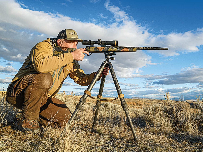 Hunter aiming a rifle in an open field.