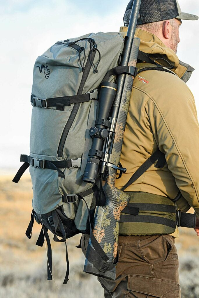 Hunter walking through a field with a backpack and rifle.