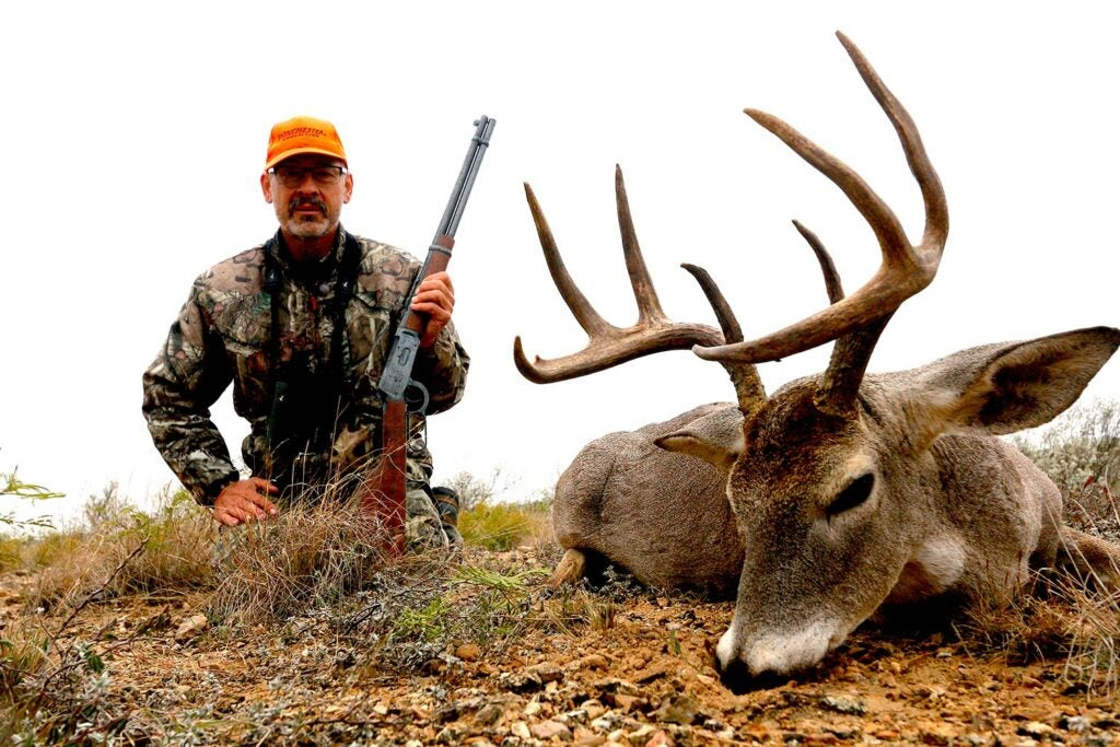 Hunter with a buck and lever-action rifle.