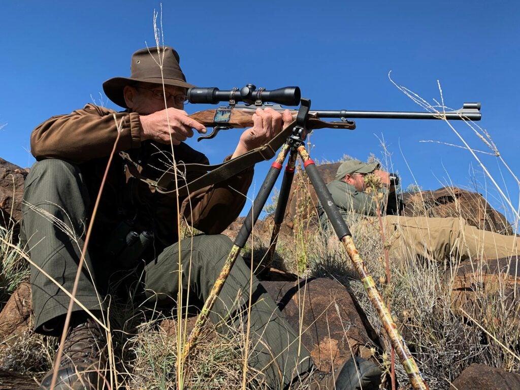 Hunter aiming a rifle using a tripod.