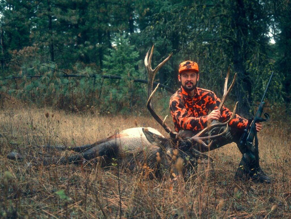 Hunter kneeling beside a large bull elk.