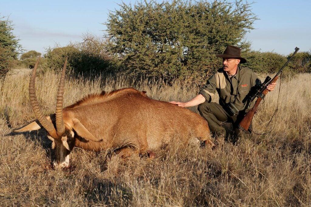Hunter kneeling beside a large South African roan.
