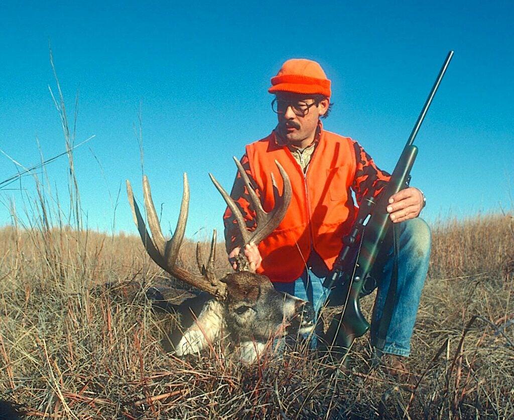 Hunter kneeling beside a whitetail buck.