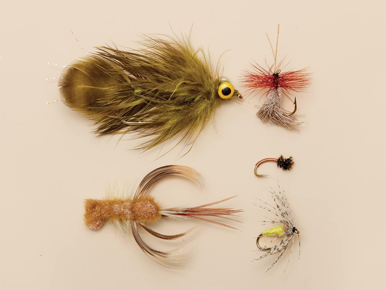 5 old school trout flies on a beige background.