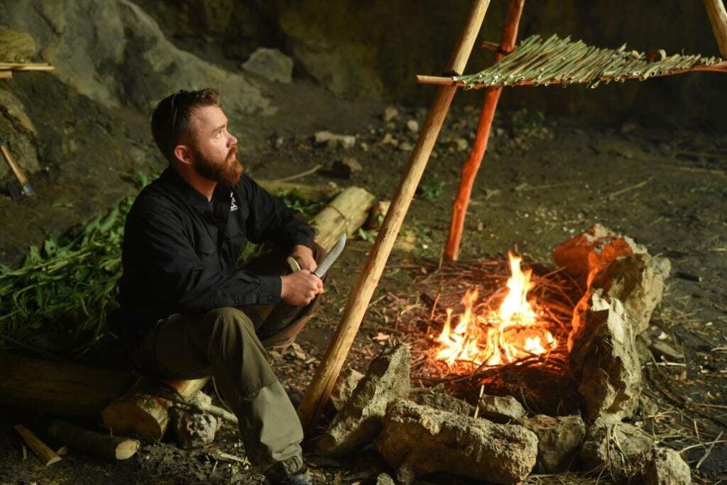 Man by a survivalist campfire.