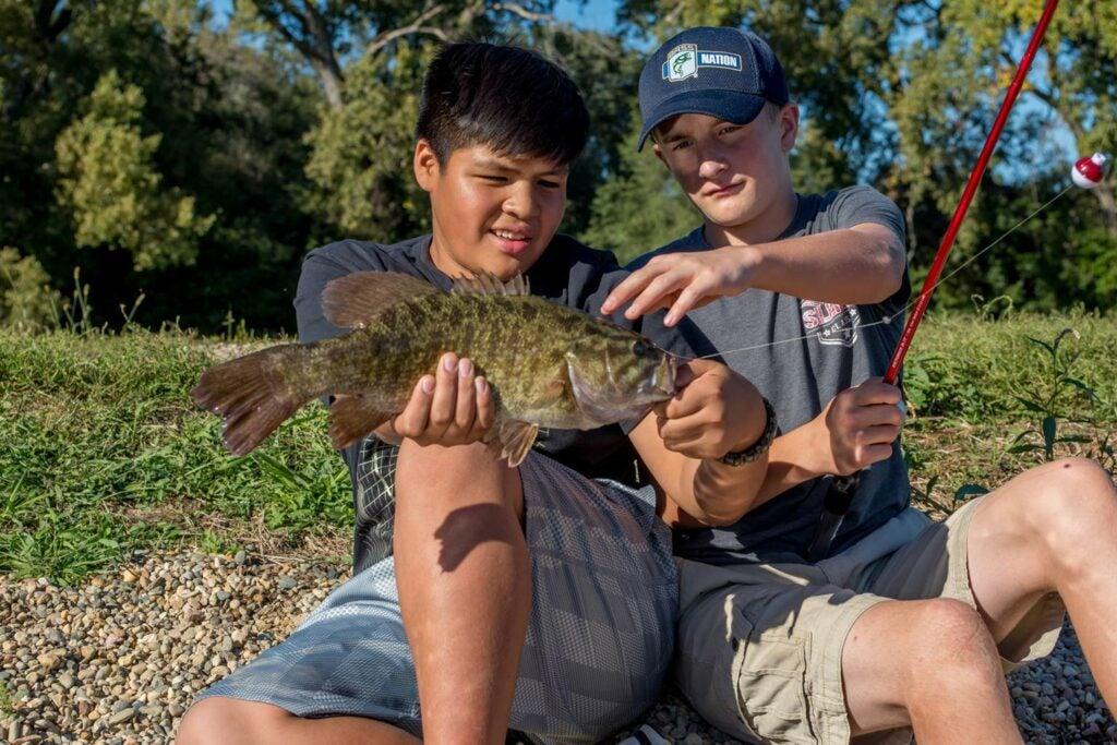 Two boys fishing bass at Lake St. Clair