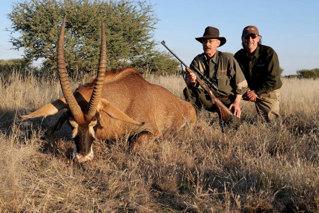 hunter next to an African pronghorn antelope.