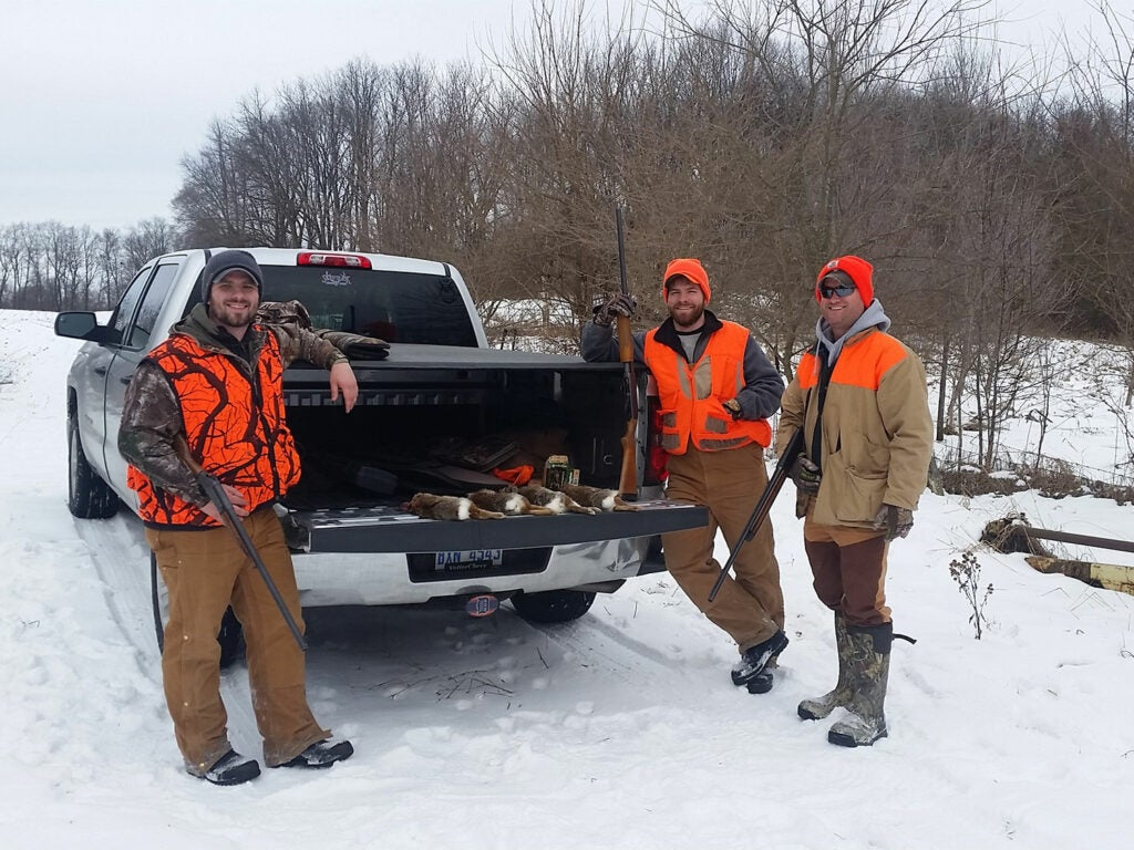 Hunters standing by a truck in the snow.