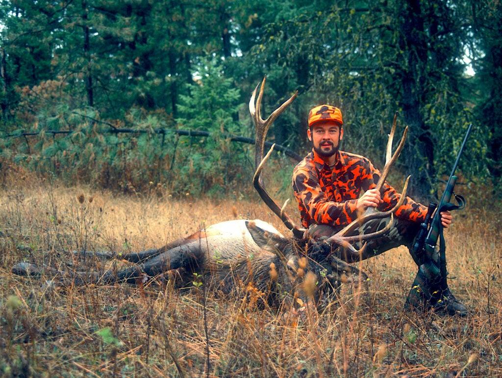 A hunter kneeling next to a bull elk.