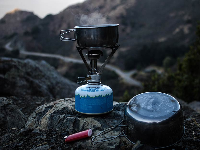 outdoor stove and cookpot on a rock.
