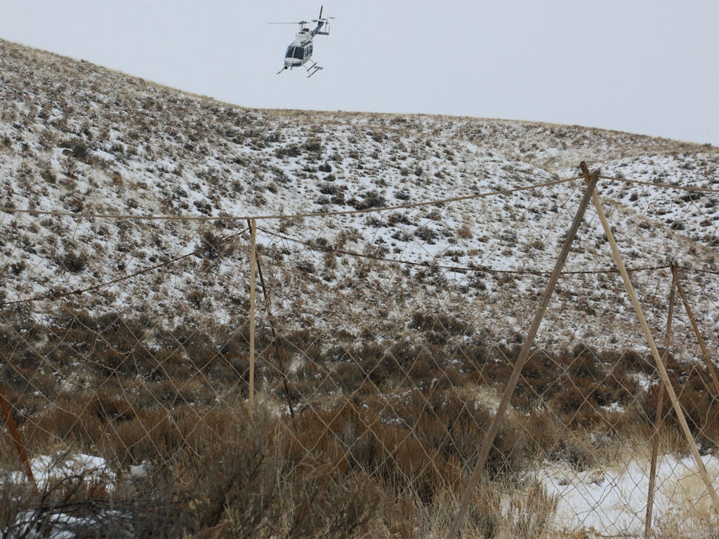A helicopter flying over a hillside covered in snow.