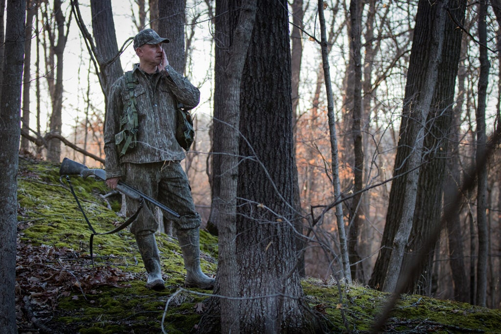 Hunter calling a turkey in the woods.