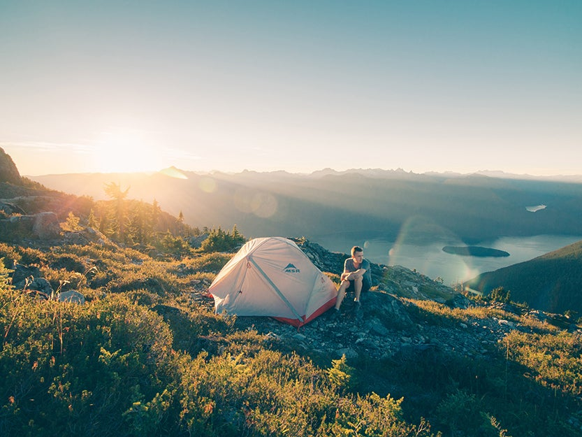 man by a campsite tent on a mountain side.