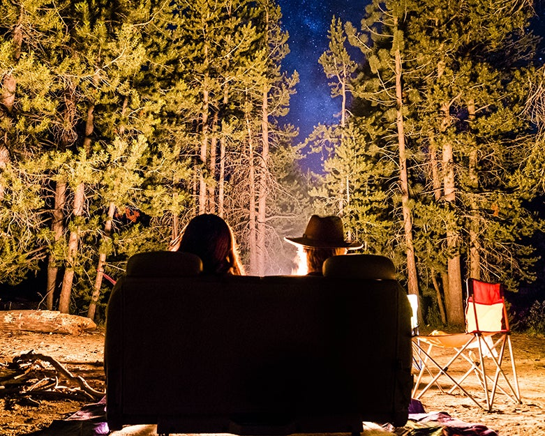 two people in a camping chair at night.