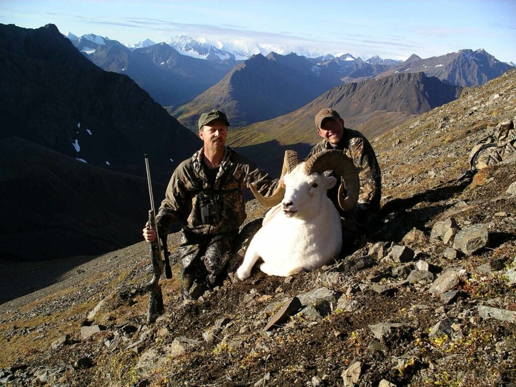 Two hunters with a dall ram.