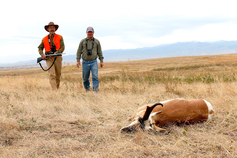 Two hunters walking through a field towards an antelope.