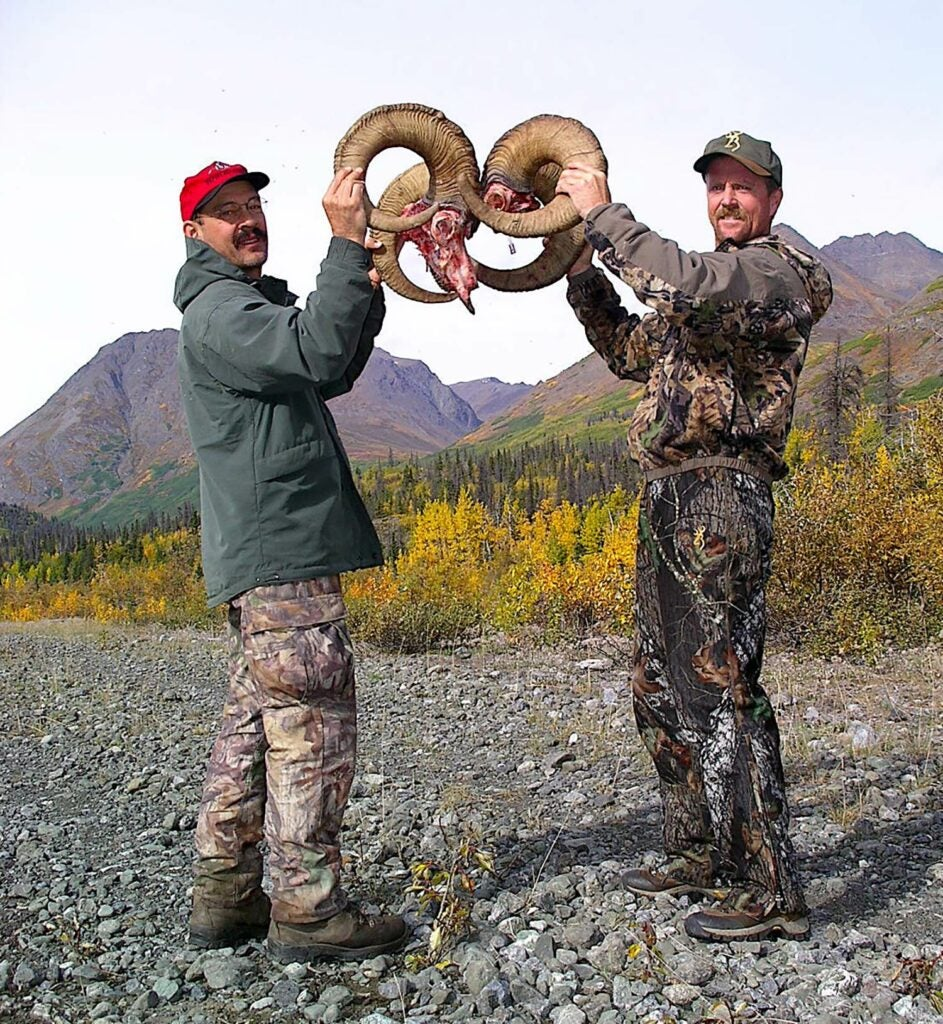Two hunters holding up ram horns.