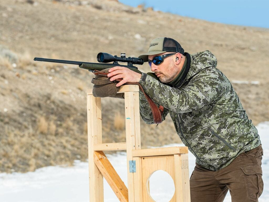 Man aiming a long-range rifle on a stand.