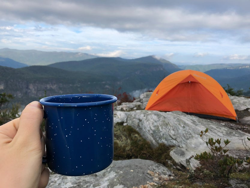 holding outdoor mug and tent.