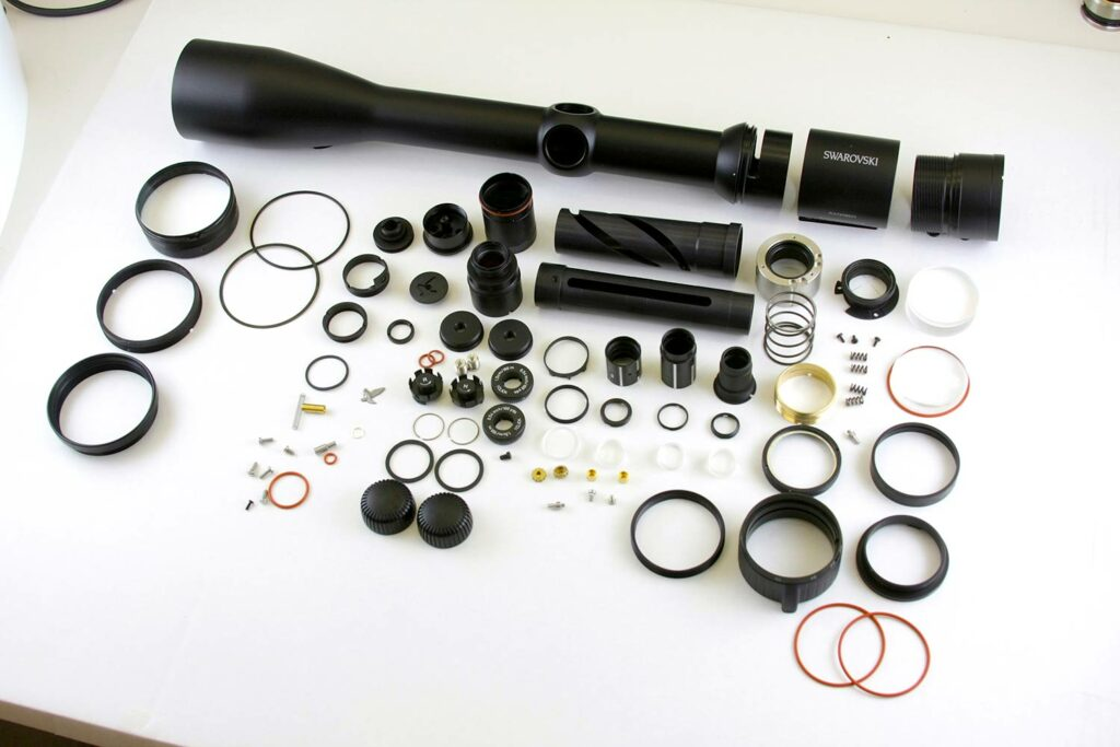 Riflescope parts on a white table.