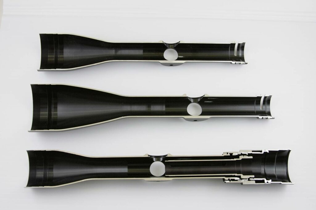 Three riflescopes on a white background.