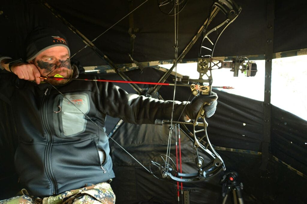 A bowhunter pulling back on a compound bow.