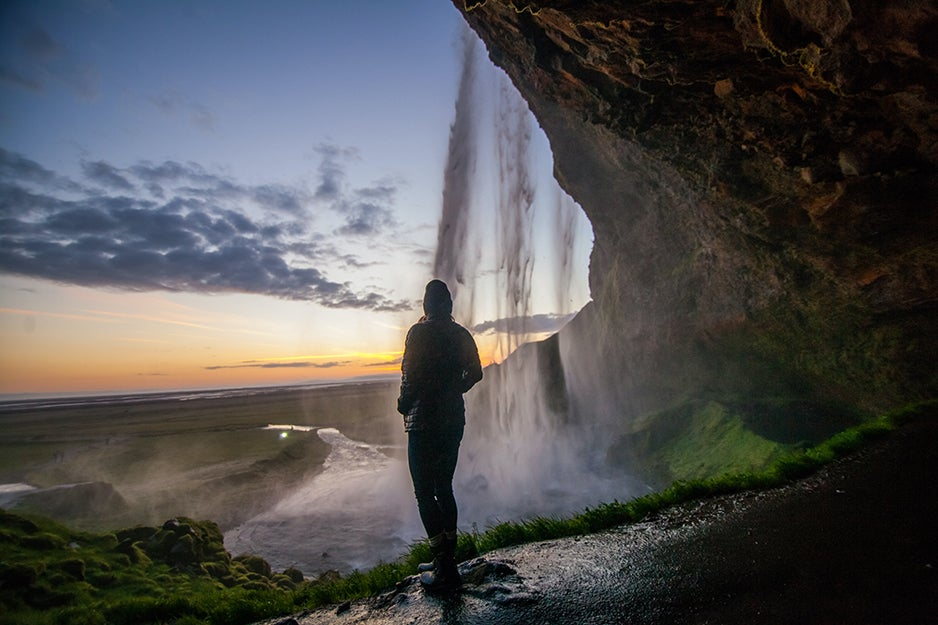 person standing under a waterfall