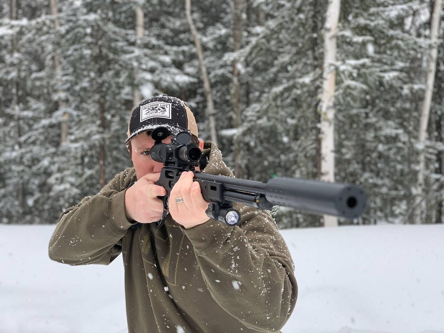 Man aiming a rifle in the snow.
