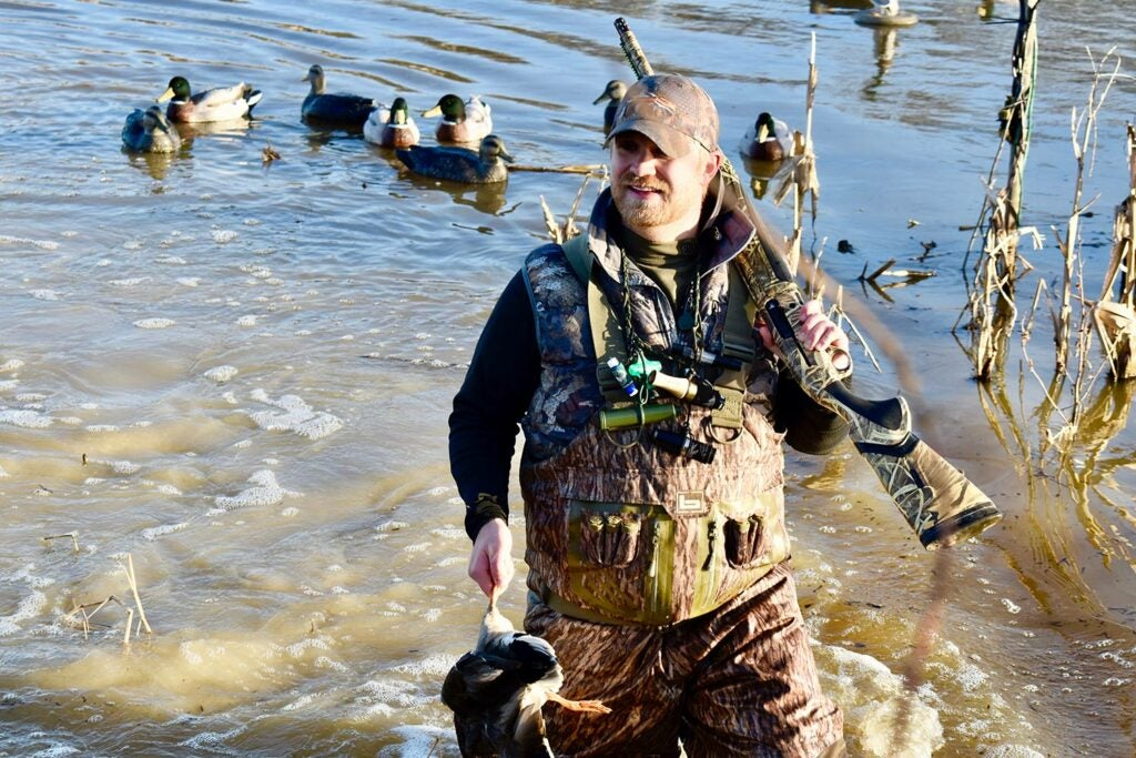 Hunter wading in a river carrying a shotgun and a duck.