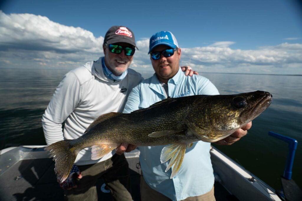 Angler holding a large walleye beside Steve Pennaz