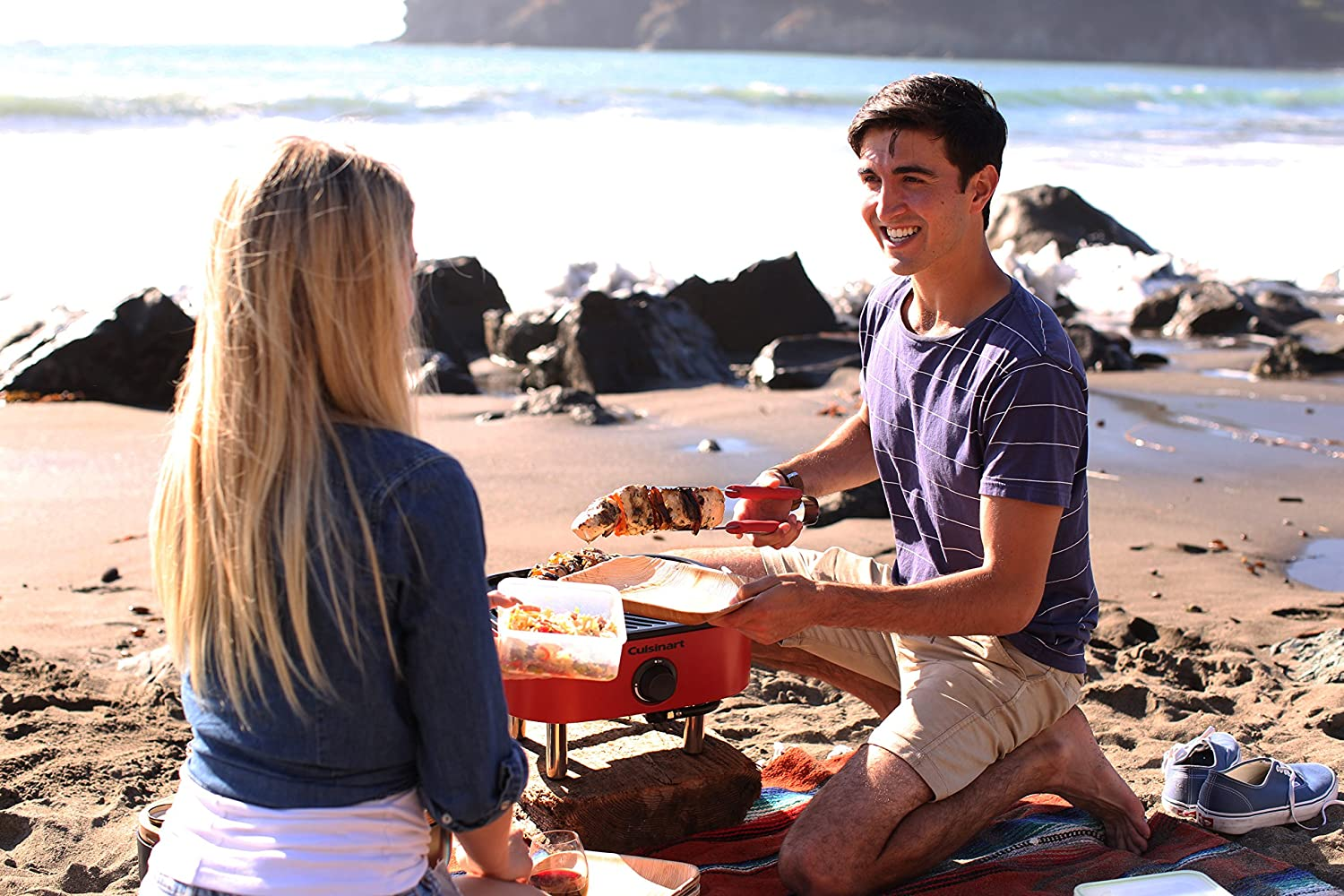 two people grilling on a beach