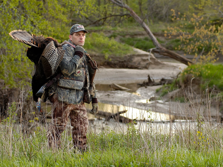 Hunter with a turkey near a river bottom.