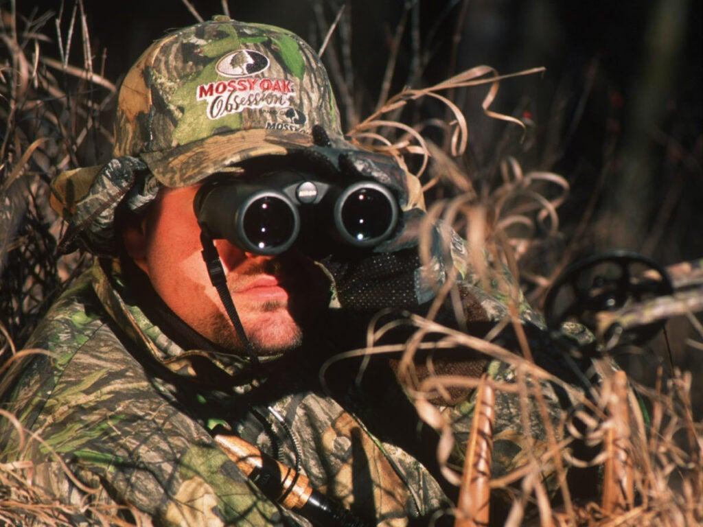A hunter glassing through binoculars.