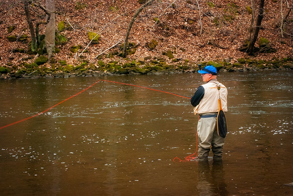 man in river with waders