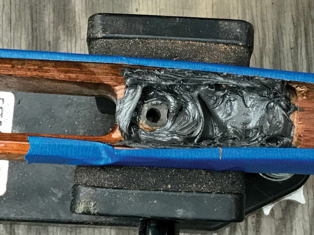 A rifle stock wrapped in blue tape.