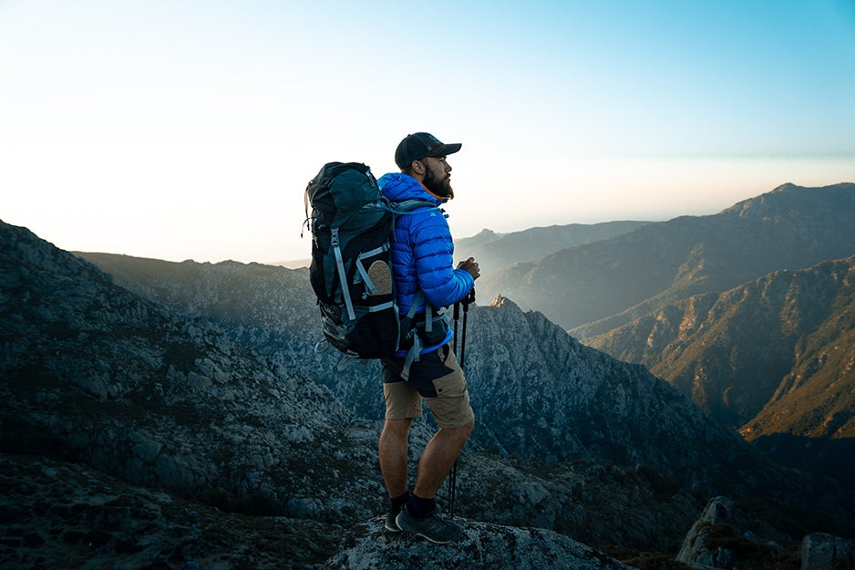 Guy on a mountain wearing a backpack
